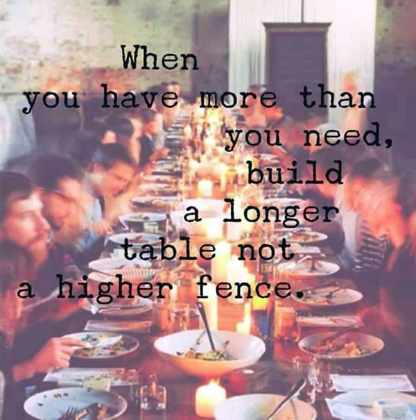 Photo of a very long table with a couple dozen people sharing a meal, captioned 'When you have more than you need, build a longer table, not a higher fence.
