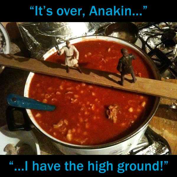 """""""It's over, Anakin! I have the high ground!"""": Obi-Wan Kenobi and Anakin Skywalker action figures fighting on a yardstick over a pot of hot chili."""
