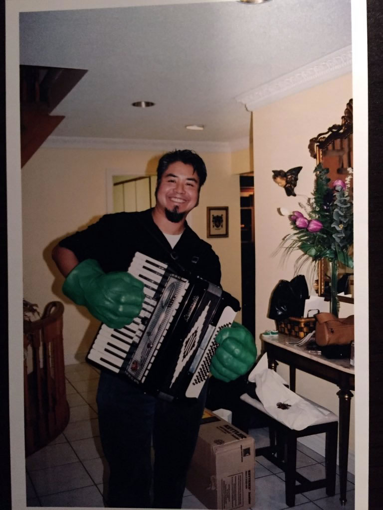 Joey deVilla plays an accordion while wearing 'Hulk Hands'.