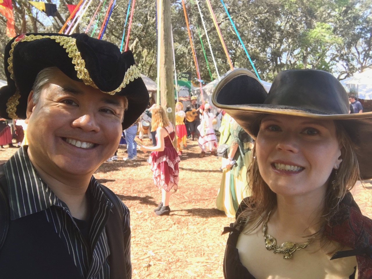 Joey deVilla and Anitra Pavka at Tampa's Bay Area Renaissance Festival in renaissance clothing, with a maypole and maypole dancers in the backgrounds.