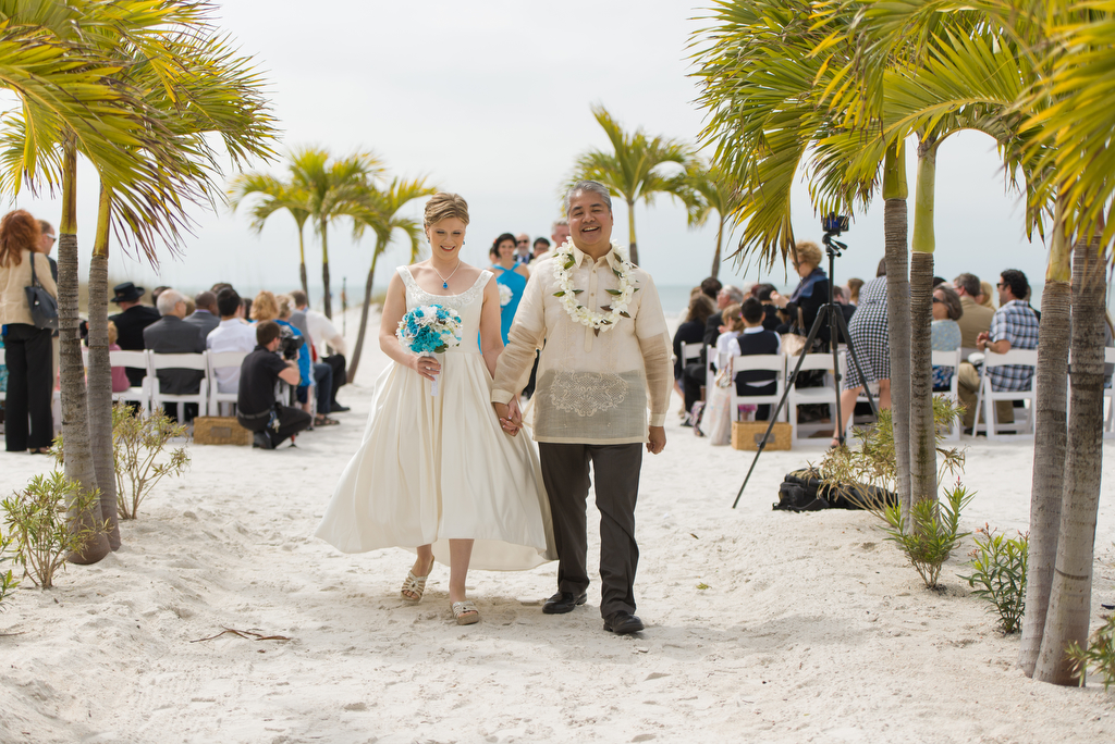 "Anitra Pavka and Joey deVilla walk down the plam tree-lined ""aisle"" of their beach wedding."