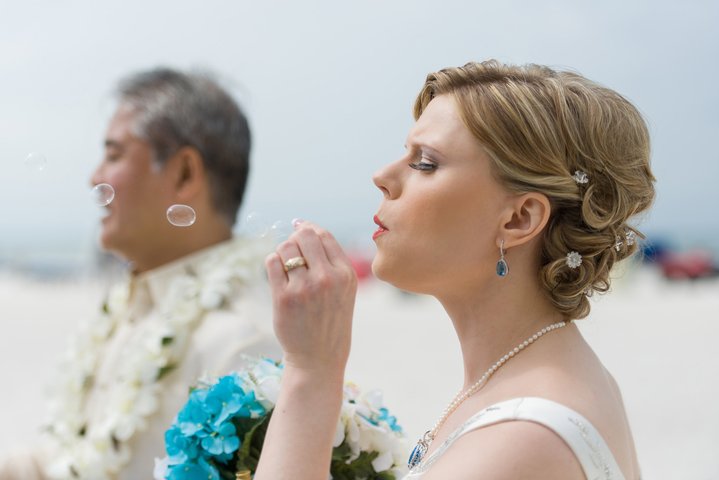 Anitra blows bubbles on the beach after the wedding ceremony