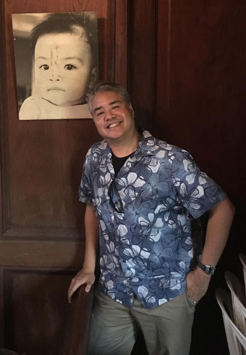 Joey deVilla posing beside his baby picture at his family's house in San Juan, Batangas, Philippines.