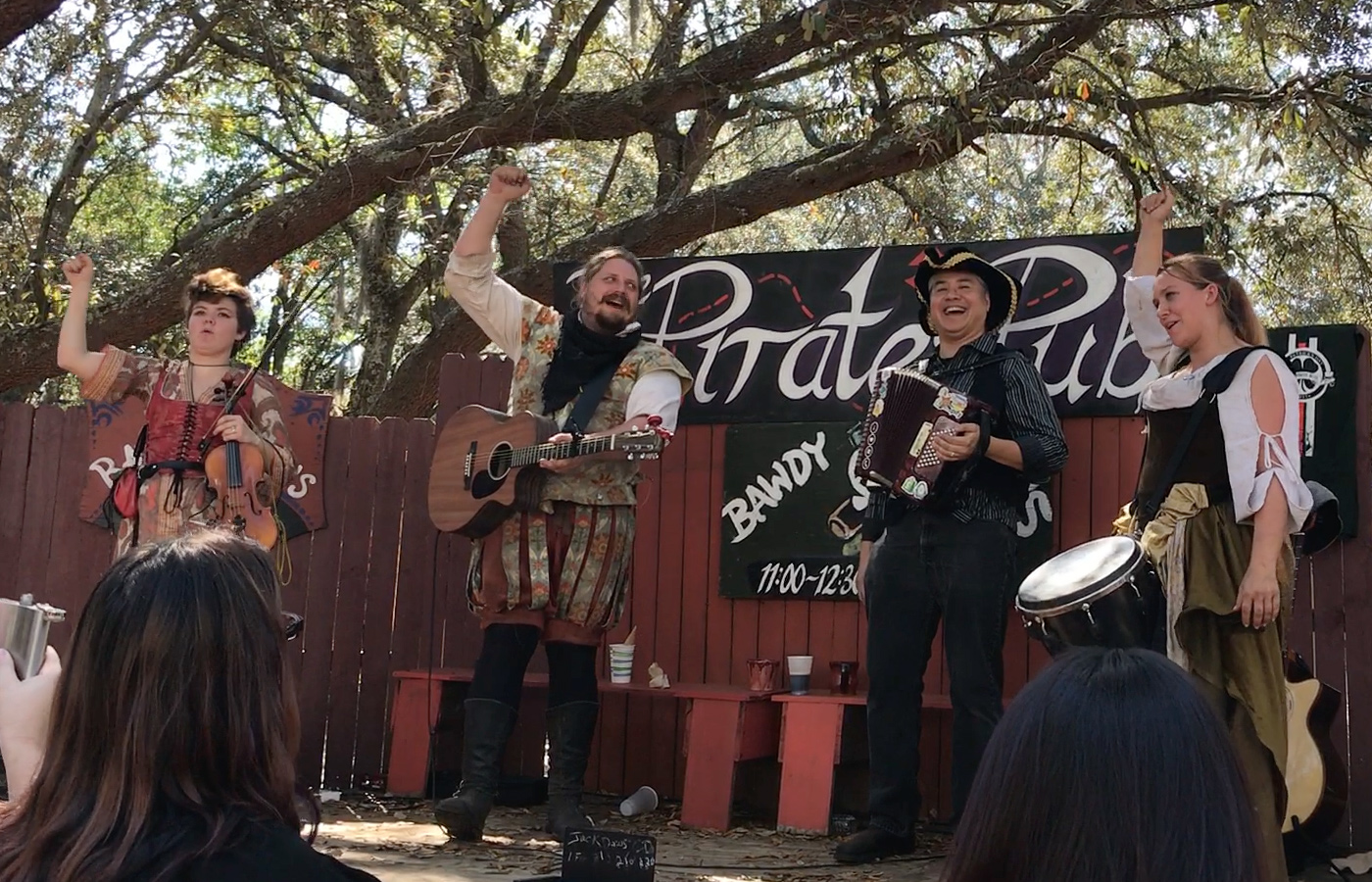 The Irish-American band The Jackdaws lead the audience with fists raised to cheer Joey deVilla. From left to right: Constance on violin, Whiplash on Guitar, Joey deVilla on accordion, and Roxy on the drum.