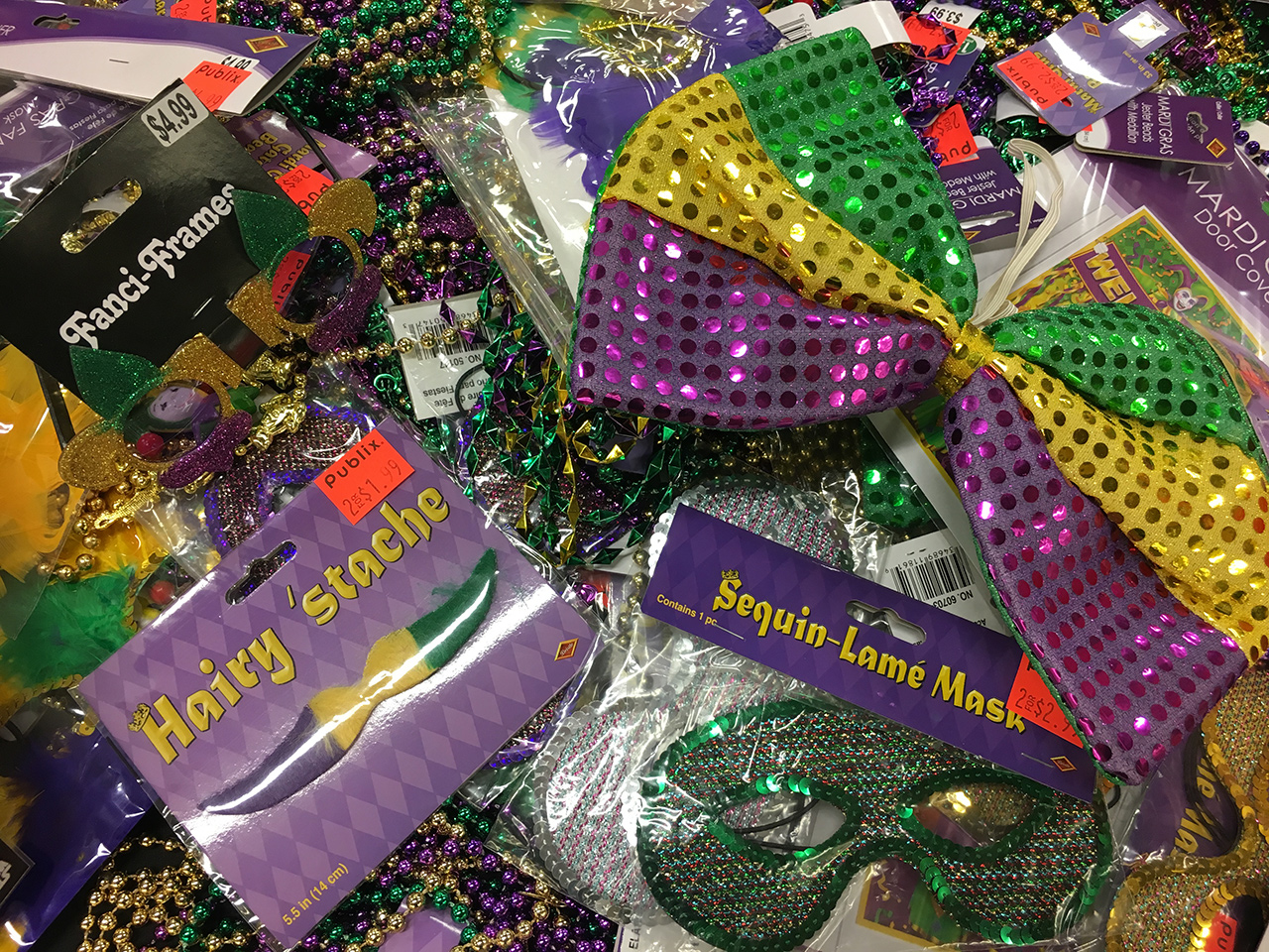 Assorted cheap Mardi Gras costumes and beads, marked down to 2 for $1.99.