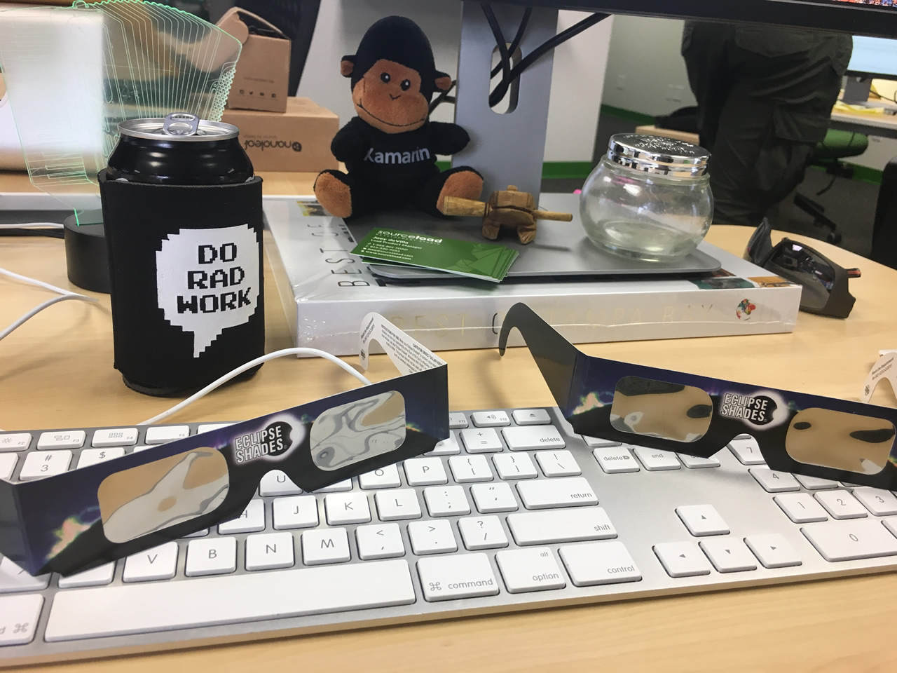 Joey deVilla's office desk, featuring solar eclipse glasses on his keyboard.