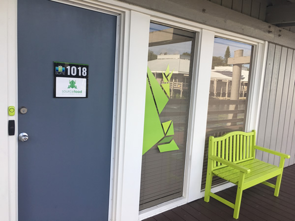 "The front door and bench outside Sourcetoad's office, which is in a ""boardwalk"" style office complex over a pond."