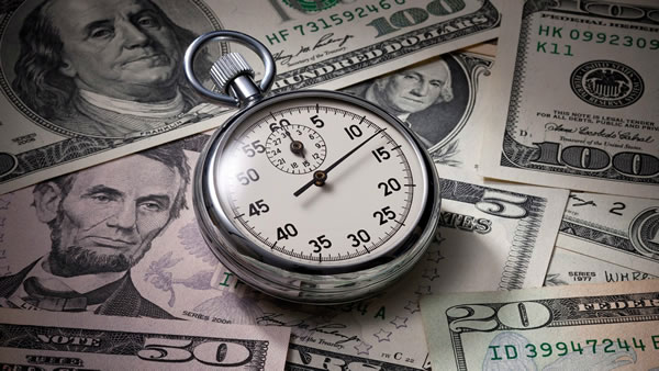 A stopwatch sitting on various denominations of US currency.