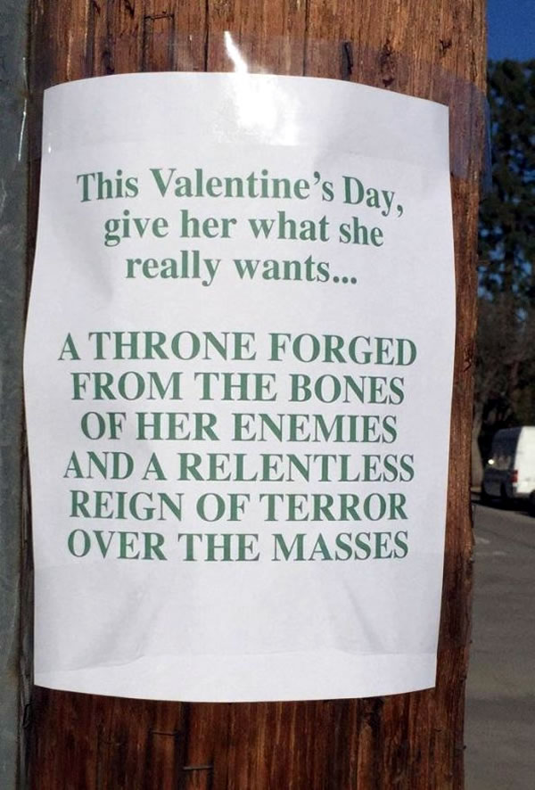 Poster on telephone pole: 'This Valentine's Day, give her what she really wants: A THRONE FORGED FROM THE BONES OF HER ENEMIES AND A RELENTLESS REIGN OF TERROR OVER THE MASSES'
