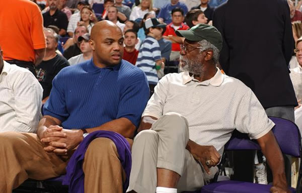 Photo: Charles Barkley and Bill Nelson, sitting side by side, conversing while watching a basketball game.