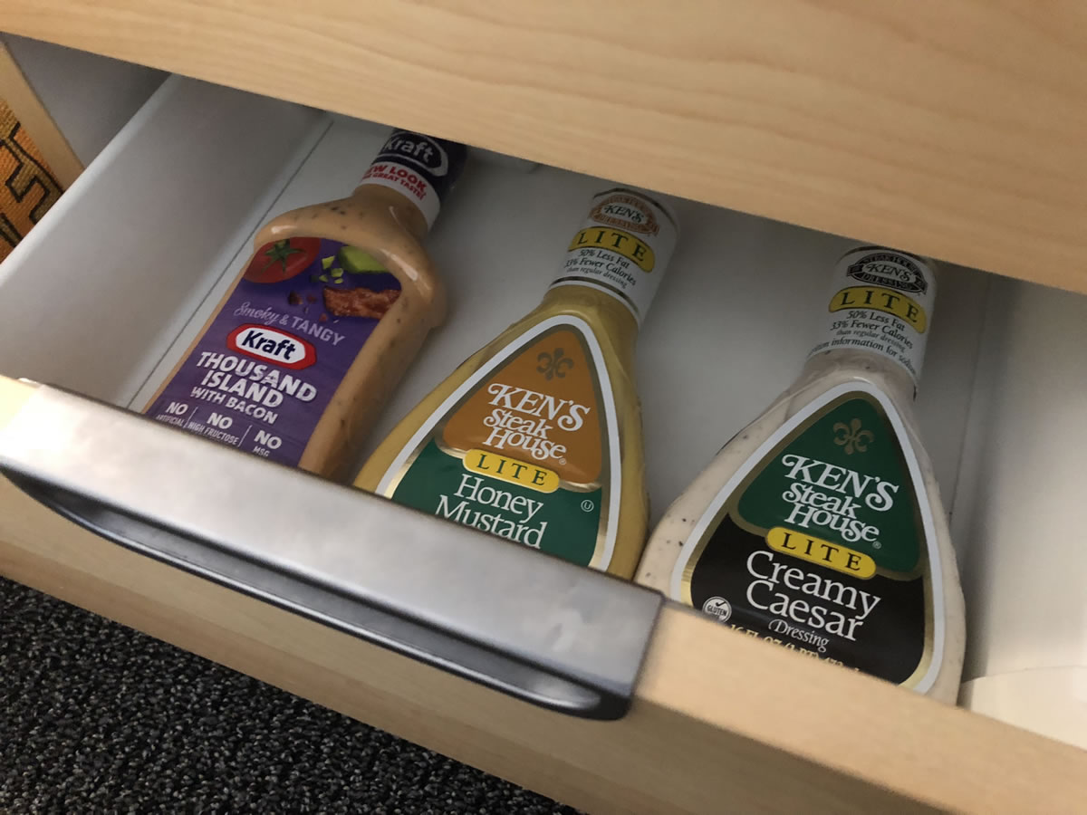 Photo: Office desk drawer open to reveal three bottles of salad dressing.