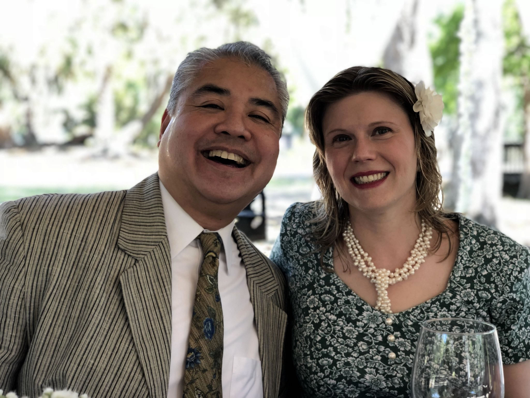 Joey deVilla in a suit and tie, smiling with Anitra Pavka in a floral dress and pearls.