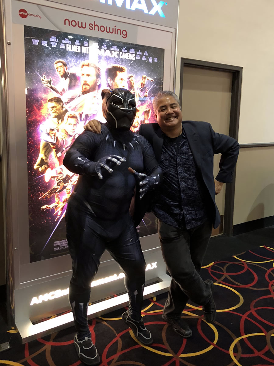 Photo: Bryan Wolfe dressed as Black Panther, posing beside Joey deVilla in front of an 'Avengers: Infinity War' poster.