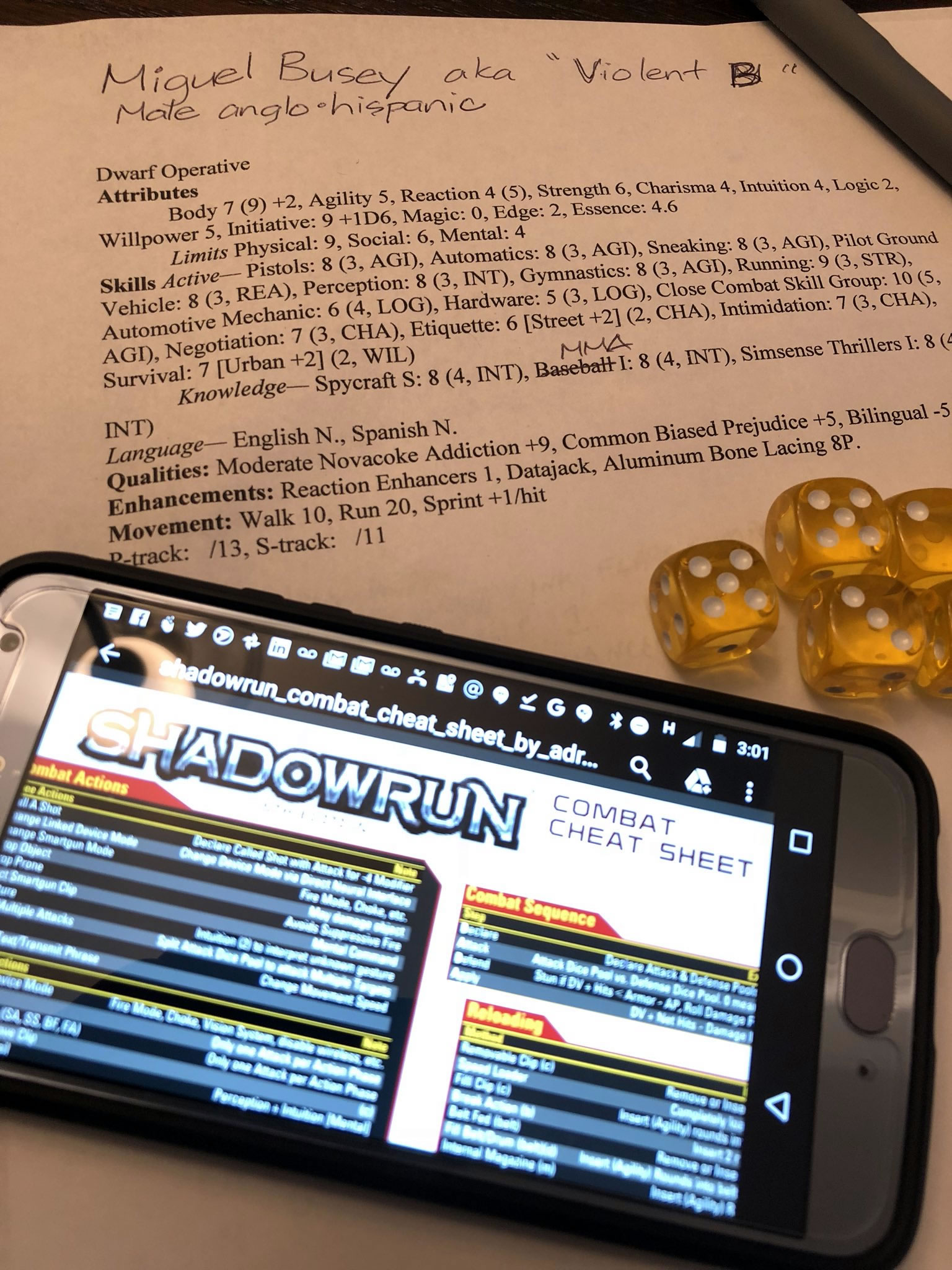 Photo: A Shadowrun still life -- character sheet for a dwarf operative with a novacoke addiction and a penchant for brawling, a handful of yellow six-sided dice, and a Motorola X4 smartphone displaying a Shadowrun cheat sheet.