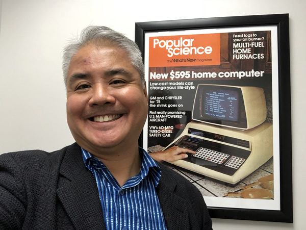 Joey deVilla smiles beside a framed poster featuring the 1977 issue of Popular Science featuring the Commodore PET 2001 computer.