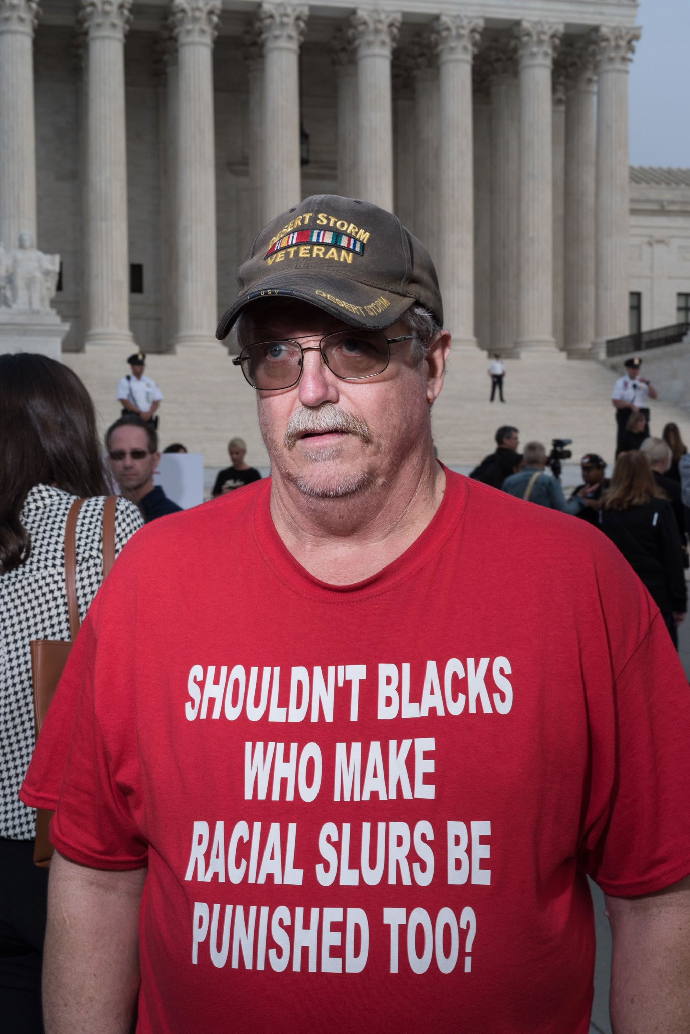 Kavanaugh supporter wearing a red t-shirt with the slogan 'Shouldn't blacks who make racial slurs be punshed too?'