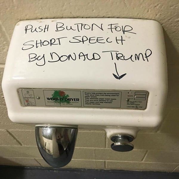 Public restroom hand dryer, with the text 'Push button for a short speech by Donald Trump' written on it.