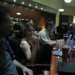 Quinn Norton sitting among other geeks at the hotel bar, all with their laptops open.