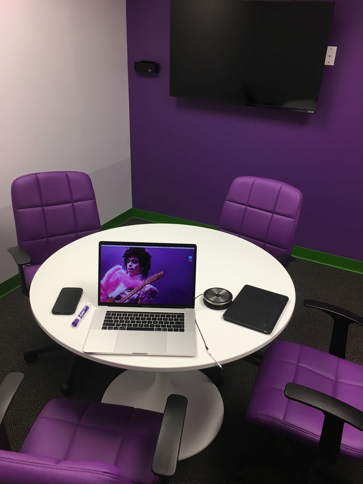 Photo: Sourcetoad's 'Purple Passion Pit' - a small room with a white table, 4 purple chairs, and a purple wall with a monitor. On the table are a purple dry-erase marker and a Macbook Pro with an image of Prince on its monitor.
