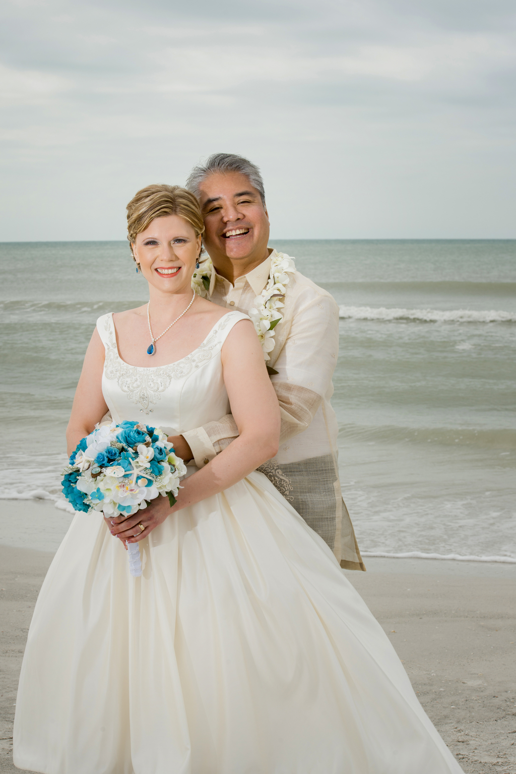 Anitra Pavka and Joey deVilla's wedding photo — Anitra posing with the beach behind them at St. Pete Beach.