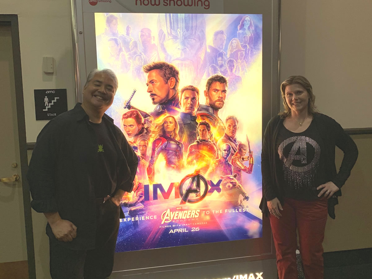 Joey deVilla and Anitra Pavka pose with the 'Avengers: Endgame' poster.