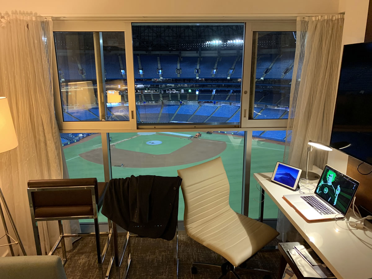 Photo: A closer-up view of the desk with my computer and iPad on it, and the interior of Rogers Centre and the baseball diamond and stands visible through the window.