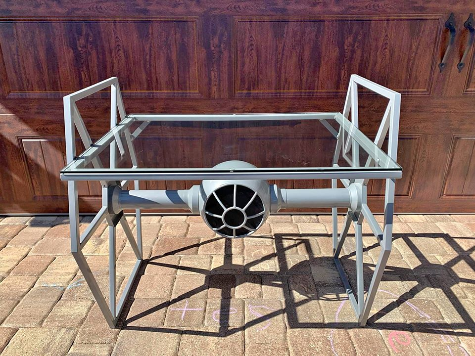 Glass-topped desk with metal frame shaped like a TIE fighter from Star Wars.