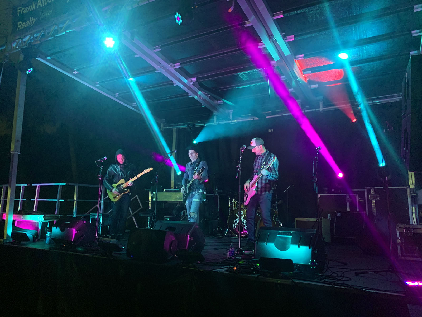The warmly-dressed guitarists and bassist from 'Have Gun Will Travel' playing onstage at River Tower Concert in evening.