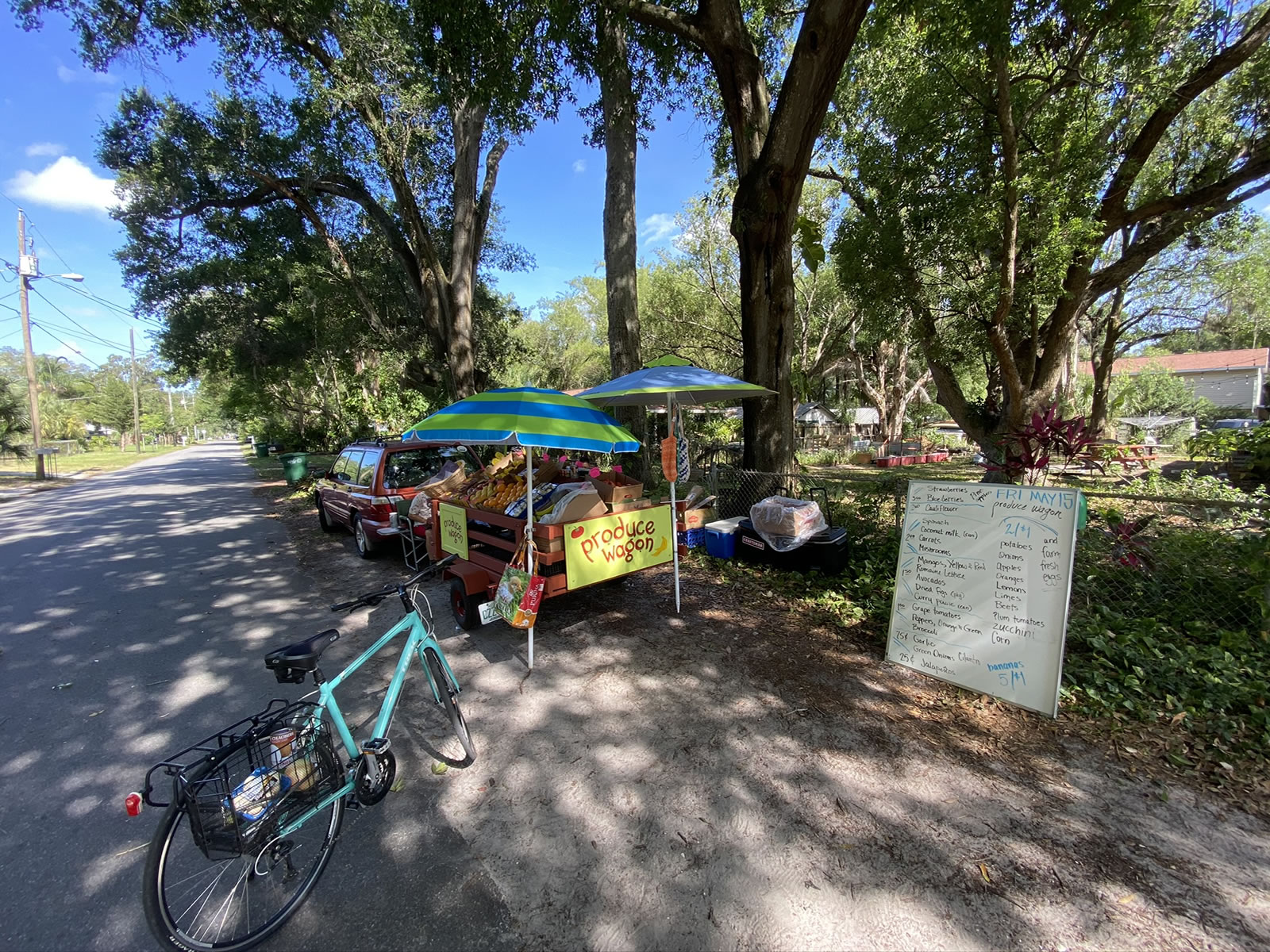 Wide-angle photo of the Produce Wagon from its right side, with Joey's light blue bicycle in the foreground, and their whiteboard price list to the right.