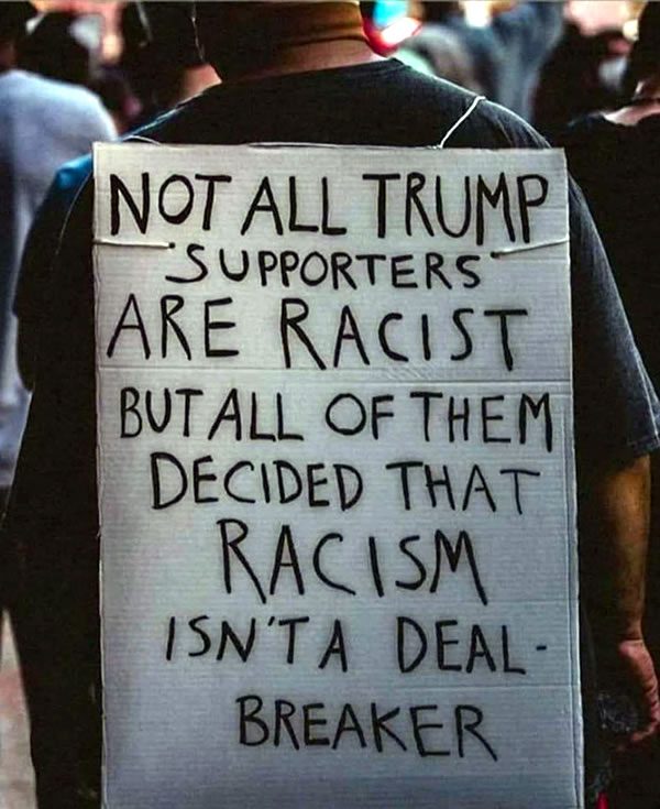 """Photo: Man wearing """"sandwich board"""" sign that reads """"Not all Trump supporters are racist, but all of them decided that racism isn't a deal-breaker""""."""