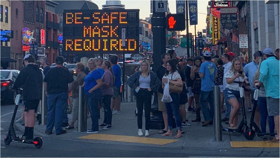 "Photo: Street scene in US city. Large highway sign reads ""Be safe - Mask required"", but nobody is the picture is wearing a mask."