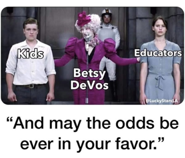 "Photo: Scene from ""The Hunger Games"" where host Effie Trinket (labeled ""Betsy DeVos"" stands between new tributes Peta Mellark (labeled ""Kids"") and Katniss Everdeen (labeled ""Educators""). The caption reads ""And may the odds be ever in your favor."""
