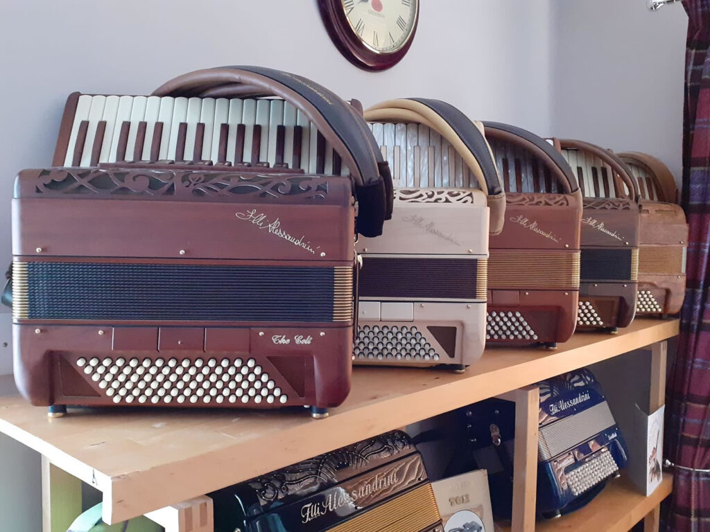 Photo: A row of Alessandrini Celt accordions in various wood finishes.