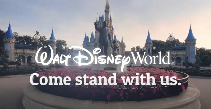 "Photo: The entrance to the Magic Kingdom park, with the Walt Disney and Mickey statue in the foreground, overlaid with the text: ""Walt Disney World / Come stand with us""."