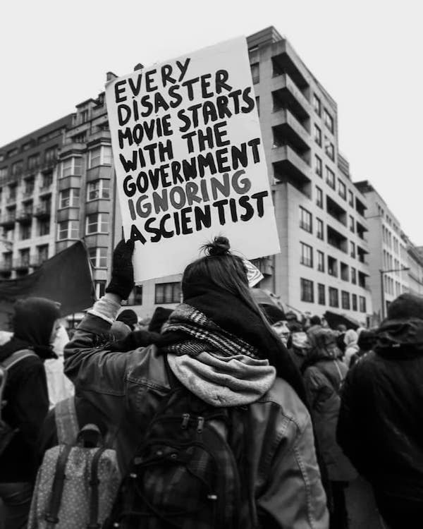 "Photo: Protestor holding up sign that reads ""Every disaster movie starts with the government ignoring a scientist""."