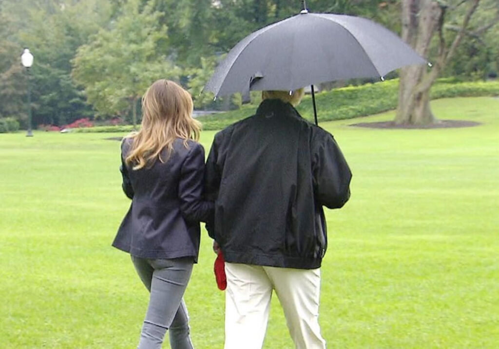 Photo: Donald and Melania Trump walking on the golf course on a misty day. Donald holds their single umbrella over himself only.