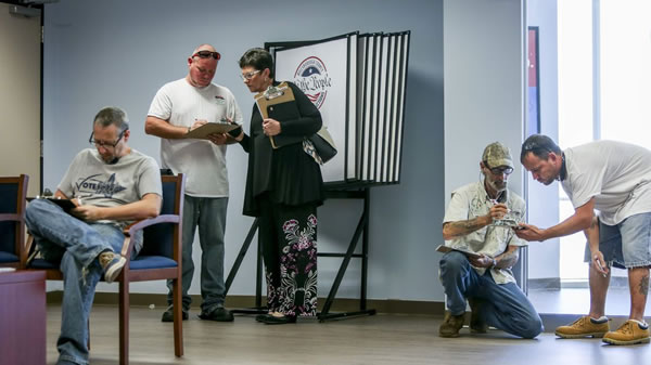 Photo: The chairwoman of Hillsborough County Democratic Party, Ione Townsend, assists people wishing to register to vote in January after regaining that right because of Amendment 4. (Photo by Tampa Bay Times)