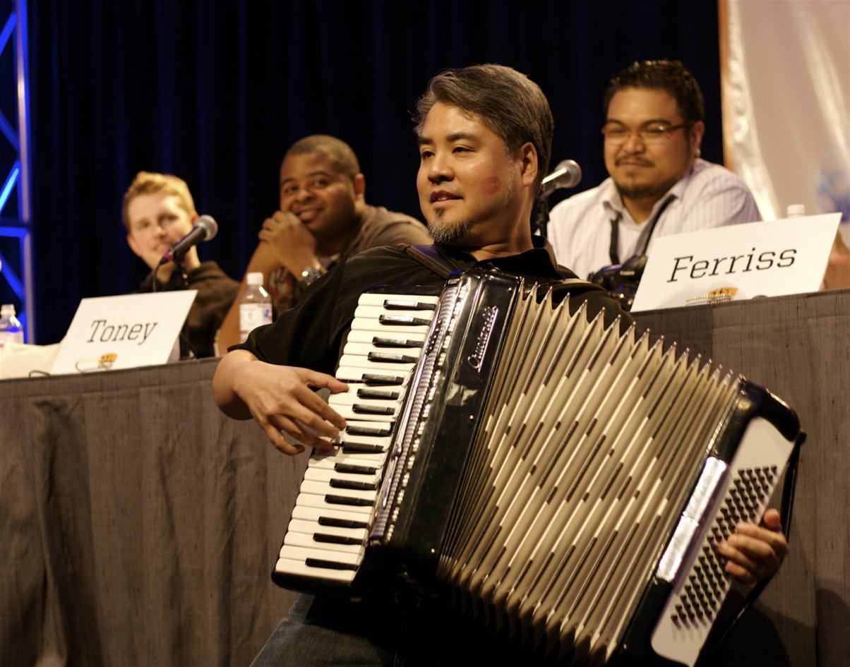 Joey deVilla plays accordion onstage in front of a panel at South by Southwest Interactive 2008 while Rannie Turingan looks on. You can see Tim Ferriss' name card (but not Tim himself).