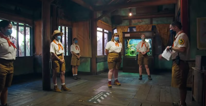 Photo: The staff of the Enchanted Tiki Room, all in surgical masks, being briefed.