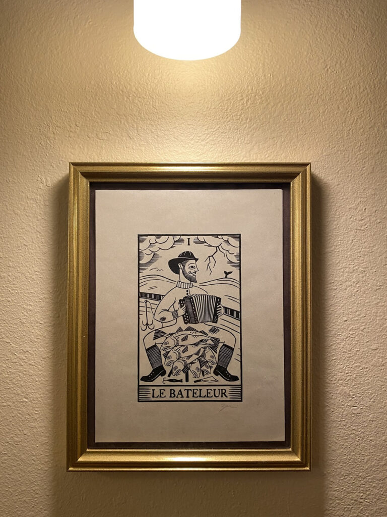 """Photo: Framed woodcut of """"Le Bateleur"""", a tarot card featuring an accordion-playing fisherman seated in front of a table overflowing with cod."""