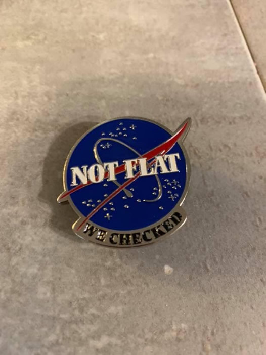 "Photo: Pin that looks like NASA pin, but says ""NOT FLAT — we checked"""