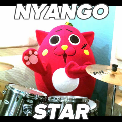"Photo: ""Nyango Star"" — a costumed mascot that looks like a cat/apple hybrid, sitting at a drum kit."