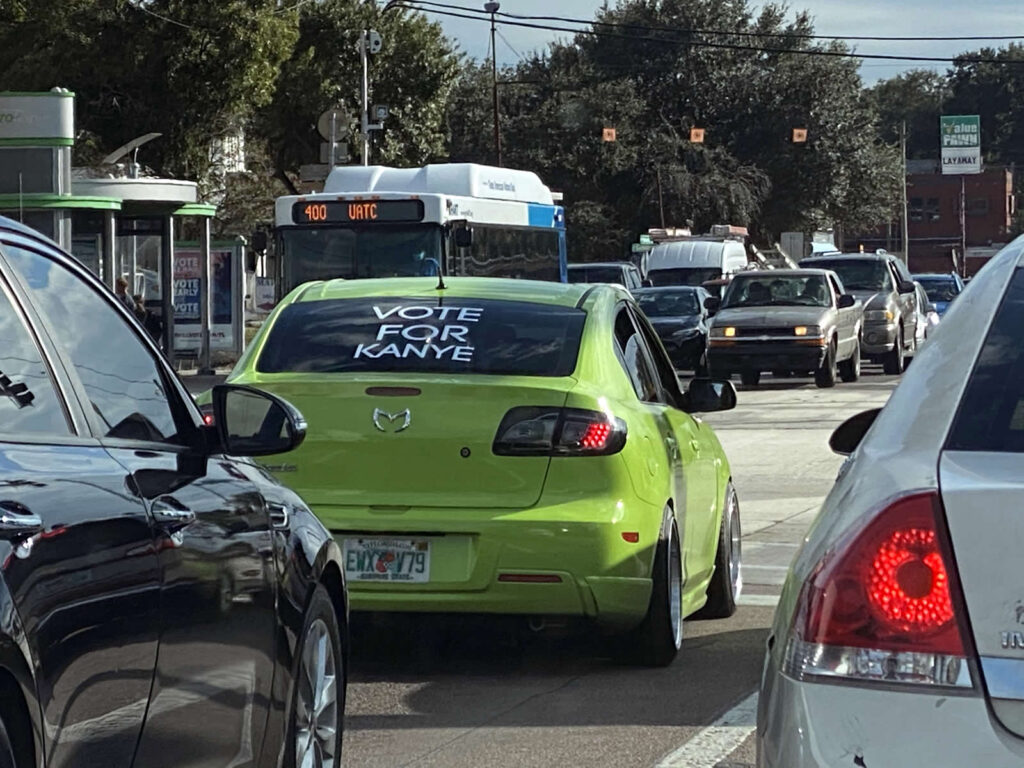 "Photo: Lime green Mazda hatchback with a big ""VOTE FOR KANYE"" sticker on its rear windshield."