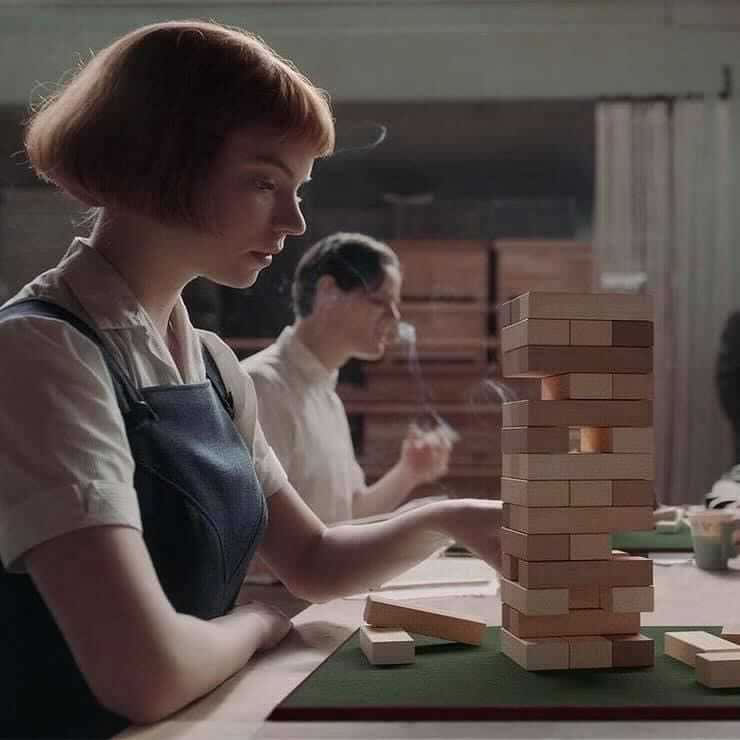 """Photo: """"Beth"""" from """"The Queen's Gambit"""" playing Jenga instead of chess."""