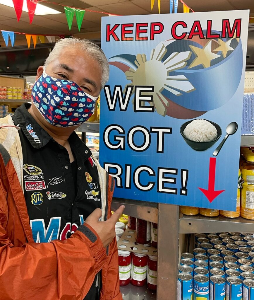 """Joey deVilla, at Tampa's Philippine Grocery, posing beside a sign that read """"KEEP CALM: WE GOT RICE!""""."""