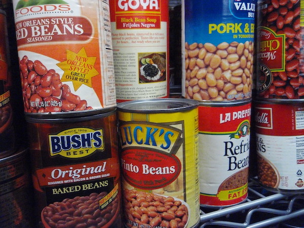Various cans of beans on a pantry shelf.