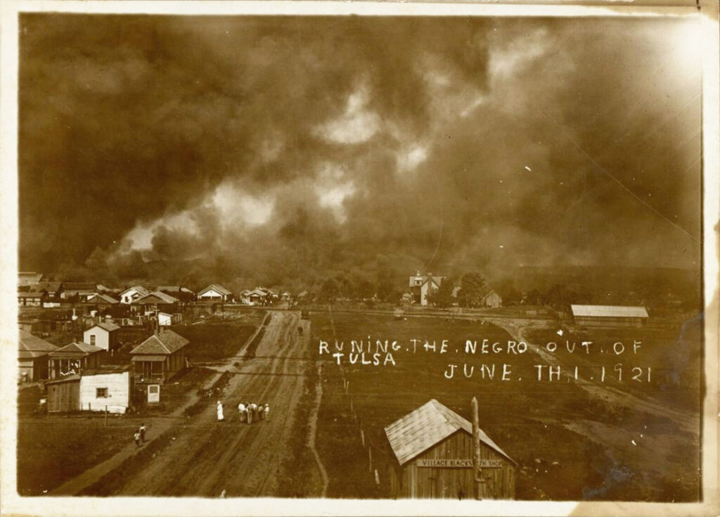 """Photo depicting a burning cityscape during the Tulsa Race Massacre on June 1, 1921. Handwritten caption reads """"Runing [sic] the negro out of Tulsa June th 1 [sic] 1921."""""""""""