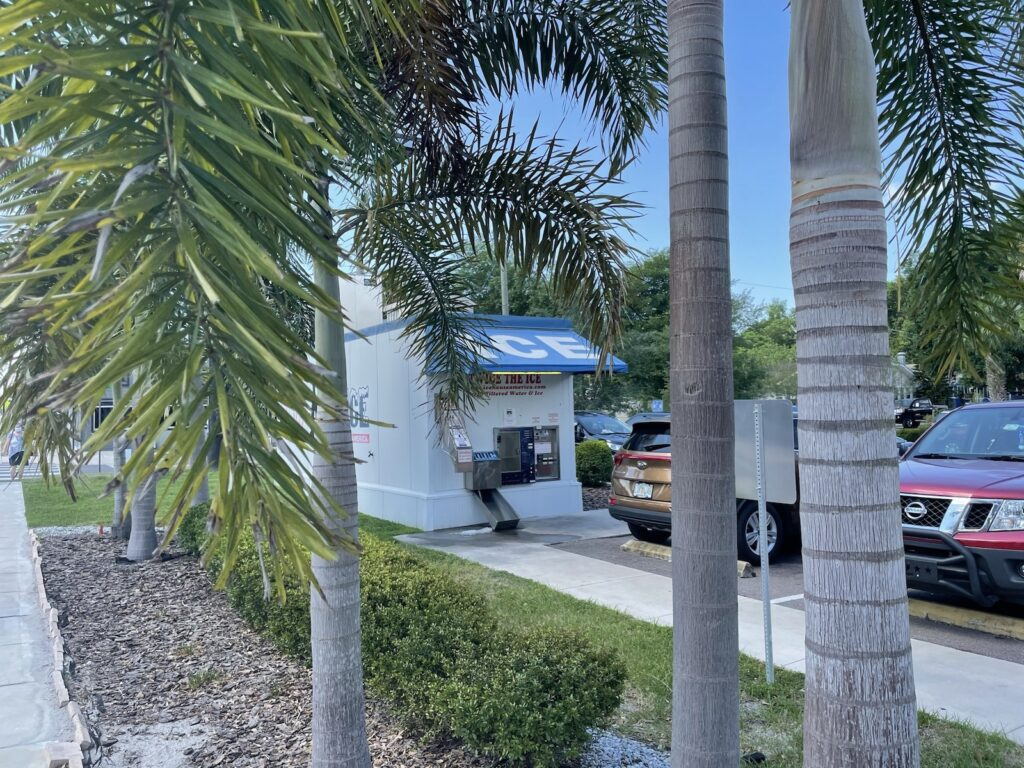 The automated ice dispensing station on Florida Avenue, as seen from the sidewalk through some palm trees.