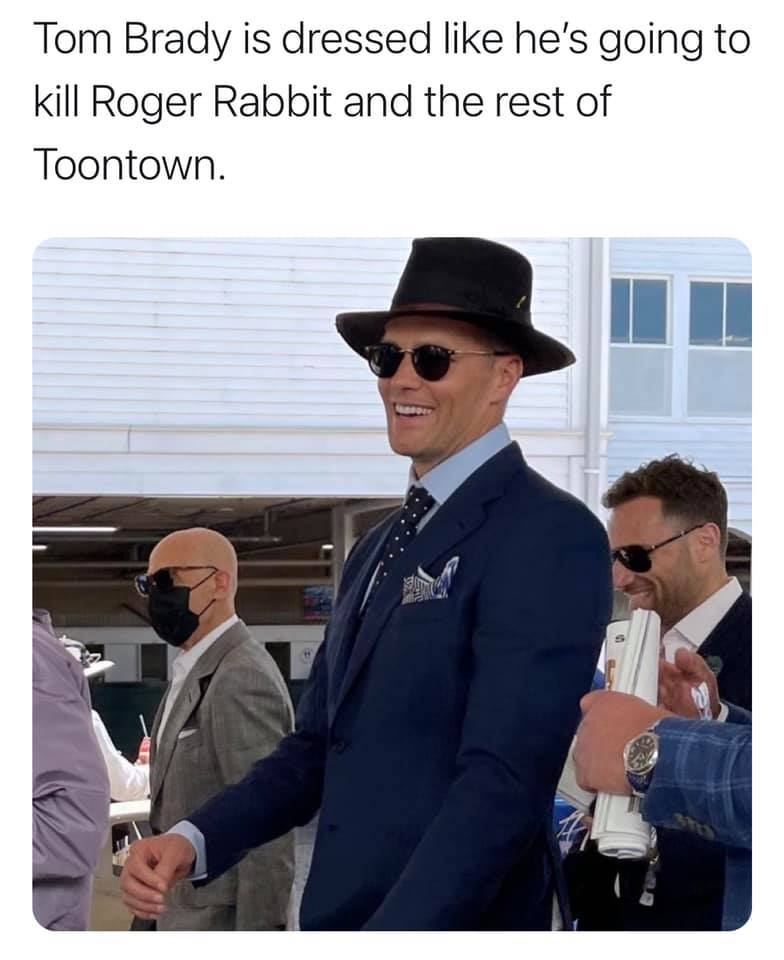 "Tom Brady wearing a black suit, black hat, white shirt, polka dotted black tie, and pocket handkerchief. Caption reads ""Tom Brady is dressed like he'd going to kill Roger Rabbit and the rest of Toontown""."