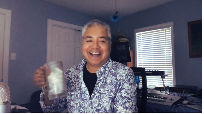 Joey deVilla at his home office, smiling and holding a big glass mug.